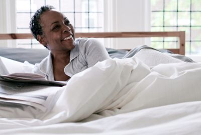 Person laying in bed enjoying soft Nestwell sheets